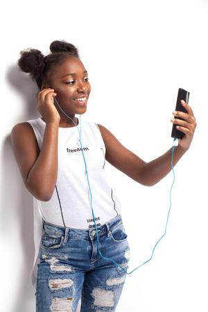 negras africanas: Adolescente joven sonriente escuchar música desde el teléfono móvil. Chica afroamericana. Estudio de disparo.