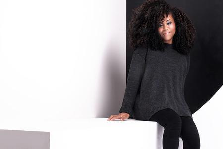 modelos negras: Muchacha africana joven hermosa americana posando en estudio, mirando a la cámara. Foto de archivo