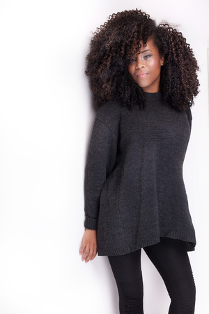 Beautiful young african american girl with afro posing in grey sweater. Studio shot. Girl smiling, looking at camera. Standard-Bild