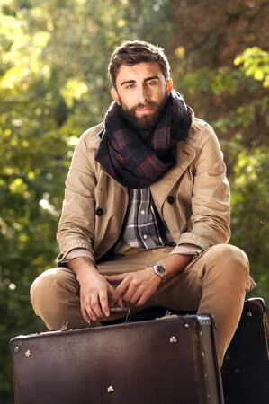 business fashion: Fashion photo of young handsome man with suitcases in park. Autumn. Men wearing coat and scarf. Sunny day. Stock Photo