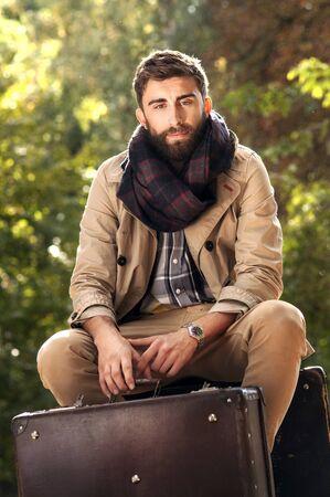 maleta: Foto de moda de joven guapo con las maletas en el parque. Oto�o. Hombres con abrigo y bufanda. Dia soleado.