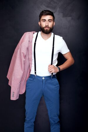 modelos hombres: Elegant young handsome man posing in studio, looking at camera. Man with beard. Foto de archivo