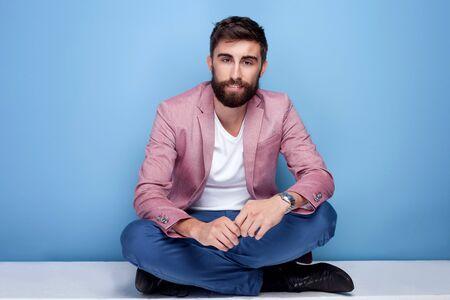 studio photo: Young handsome man sitting on the floor. Fashion photo. Studio shot.