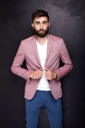 casual men: Elegant young handsome man posing in studio, looking at camera. Man with beard. Stock Photo