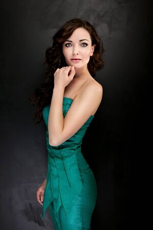 glamour makeup: Beautiful elegant young woman posing in dress. Girl with long curly hair and glamour makeup. Studio shot. Fashion photo.