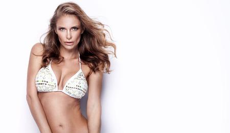 hot breast: Красивая молодая сексуальная женщина позирует в купальники, глядя на камеру. Студия выстрел. Белый фон. Фото со стока