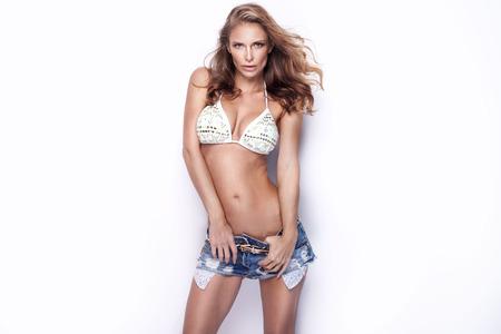 hot breast: Красивая молодая сексуальная женщина позирует в короткие джинсы и купальники, глядя на камеру. Студия выстрел. Белый фон. Фото со стока