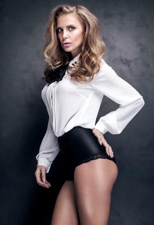 junge nackte m�dchen: Reizvolle elegante blonde Frau posiert im Studio. Schwarzem Hintergrund. Sch�ne Gesch�ftsfrau mit Brillen.