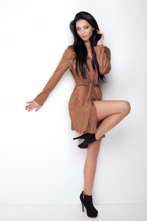 Young beautiful woman with long black hair posing im studio, wearing brown fashionable coat. Girl smiling and looking at camera.