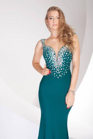 Elegante bella donna in posa in abito da sera alla moda, guardando a porte chiuse. Studio girato.