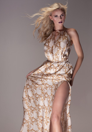 maxi dress: Beautiful blonde woman posing in studio , wearing fashionable maxi dress, looking at camera. Elegant style.