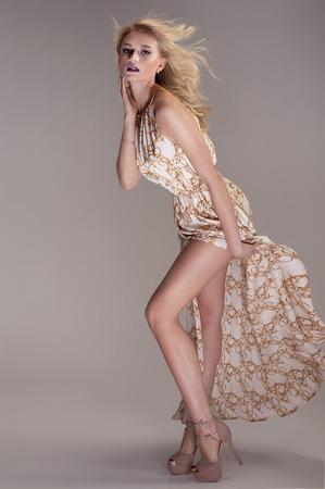 maxi dress: Beautiful blonde woman posing in studio , wearing fashionable maxi dress, looking at camera. Elegant style.