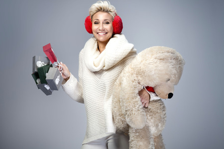 birthday teddy bear: Smiling beautiful adult woman holding big teddy bear. Looking at camera. Studio shot. Winter style. Stock Photo