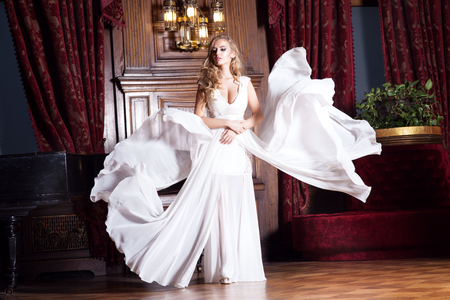 white girl: Beautiful young woman with long curly hair posing in white wedding dress in luxury palace. Attractive bride .