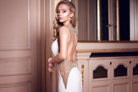 hair curly: Joven y bella mujer con el pelo largo y rizado posando en traje de novia blanco en el palacio de lujo. Novia atractiva.