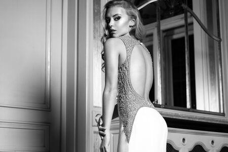 Giovane e bella donna con lunghi capelli ricci in posa in bianco abito da sposa nel palazzo di lusso. Sposa attraente.