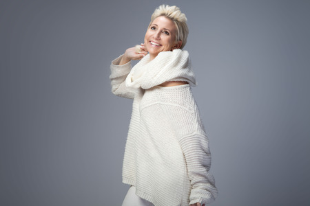 vogue style: Beautiful adult blonde woman with short hair posing in studio, smiling. Lady wearing sweater and scarf. Stock Photo