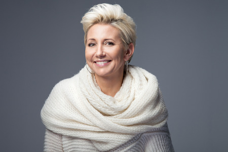 Beautiful adult blonde woman with short hair posing in studio, smiling. Lady wearing sweater and scarf.
