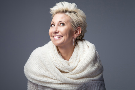 Beautiful adult blonde woman with short hair posing in studio, smiling. Lady wearing sweater and scarf. Фото со стока