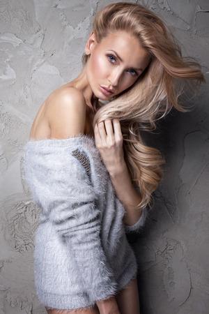 Schöne blonde Frau posiert in modische Pullover, Blick in die Kamera. Glamour Make-up, lange gesundem Haar.