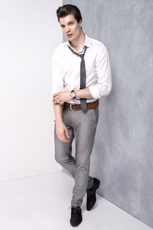 hombre de negocios joven elegante que presenta en el estudio, mirando a la cámara. Hombre guapo.