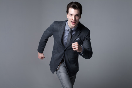 Running businessman. Studio shot. Succesfull young handsome man in elegant suit.