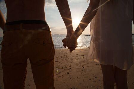 Foto de verano, pareja tomados de la mano, caminando en la playa. Puesta de sol.