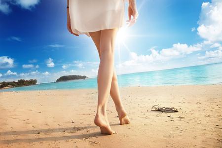 Schöne Frau, die Beine auf dem Strand, Thailand. Lizenzfreie Bilder