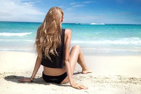 Junge blonde Frau sitzt am Strand, Blick auf das Meer. Sommer-Foto. Thailand.