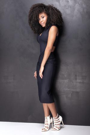 African American junge schöne Mädchen posiert im eleganten Kleid, Blick in die Kamera. Mädchen mit Afro. Studio gedreht.