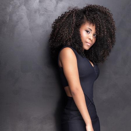 Jonge mooie African American meisje poseren in een elegante jurk, camera kijken. Meisje met afro. Studio-opname.