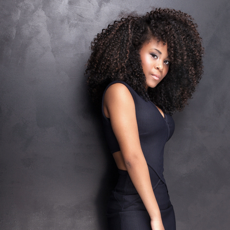 Young beautiful african american girl posing in elegant dress, looking at camera. Girl with afro. Studio shot.