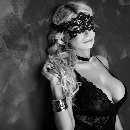 breasts erotic: Sexy beautiful blonde woman posing in elegant black lingerie and mask, looking at camera. Perfect body.