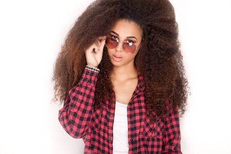 mujeres morenas: Retrato de la sonrisa hermosa muchacha afroamericana con el pelo largo y rizado. Chica con gafas de sol. Foto de archivo