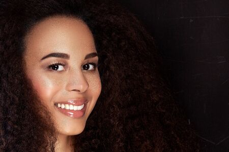 Beauty portrait of young attractive african american girl with toothy smile. Long curly hair. Girl looking at camera. Stock Photo