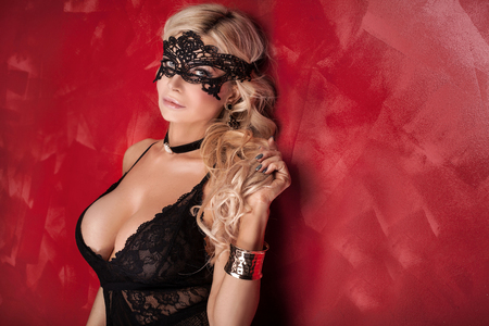 erotic breast: Sexy beautiful blonde woman posing in elegant black lingerie and mask, looking at camera. Perfect body. Red background.