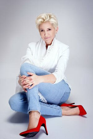 Fashionable blonde adult woman posing in studio, wearing jeans and red high heels. Short hairstyle.