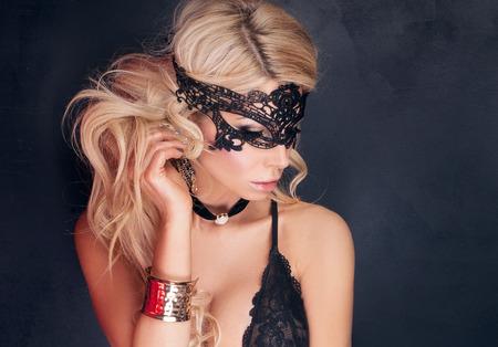 Reizvolle schöne blonde Frau im eleganten schwarzen Dessous und Maske posiert. Perfekter Körper.
