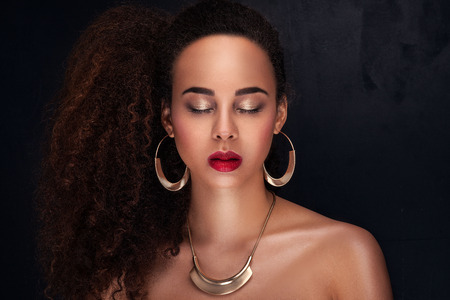 Fashion photo of beautiful elegant african american woman. Girl posing in jewelry, wearing fashionable earrings and necklace. Beauty portrait. Studio shot.