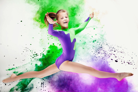 Happy beautiful gymnastic girl. Studio background.