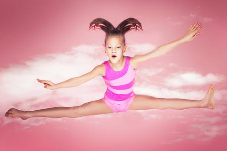 Happy beautiful gymnastic girl. Studio background. Pink. Stock Photo