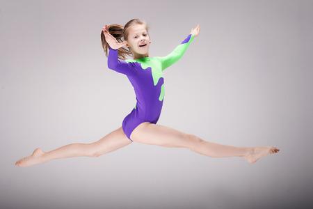 Happy beautiful gymnastic girl. Studio background.