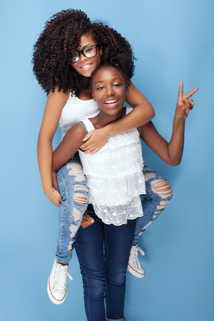 Two beautiful african american girls smiling, looking at camera. Sisters posing on blue background. Studio shot.Girls having fun.