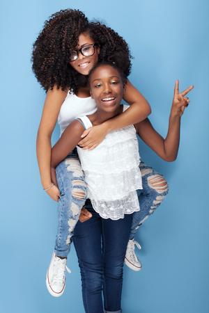 Zwei schöne African American Mädchen lächelnd und blickte in die Kamera. Schwestern auf blauem Hintergrund aufwirft. Studio shot.Girls Spaß haben.
