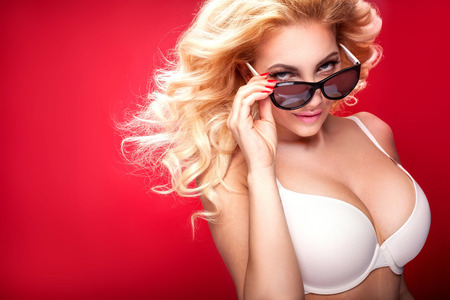 nude woman standing: Beautiful blonde natural woman posing in white lingerie and sunglasses. Ideal slim body. Red background.