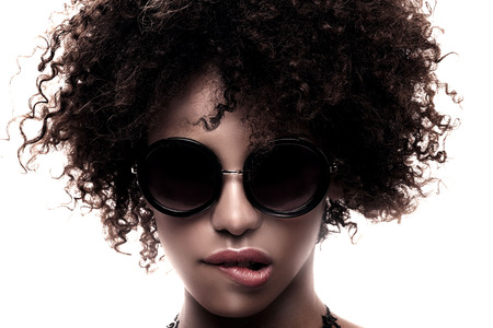 Beauty closeup portait of young stylish african american girl with afro. Girl wearing fashionable sunglasses and necklace.