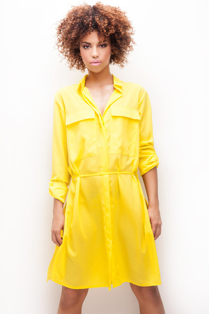 Sexy beautiful African American girl posing in yellow fashionable dress. Woman with afro and glamour makeup. Studio shot.