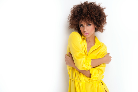 african american sexy: Portrait of beautiful young African American woman with afro and glamour makeup. Studio shot. Yellow fashionable dress.