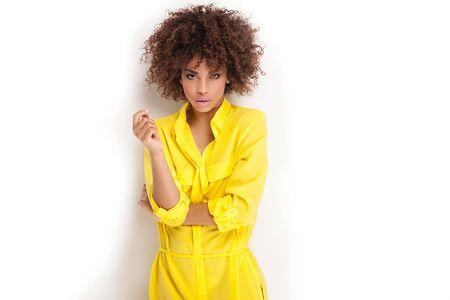 Portrait der schönen jungen afroamerikanischen Frau mit Afro und Glamour Make-up. Studio gedreht. Gelb modische Kleidung.