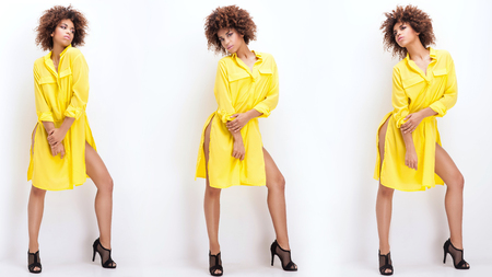american: Sexy beautiful African American girl posing in yellow fashionable dress. Woman with afro and glamour makeup. Studio shot.